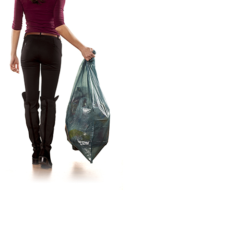 Woman from behind carrying a garbage bag