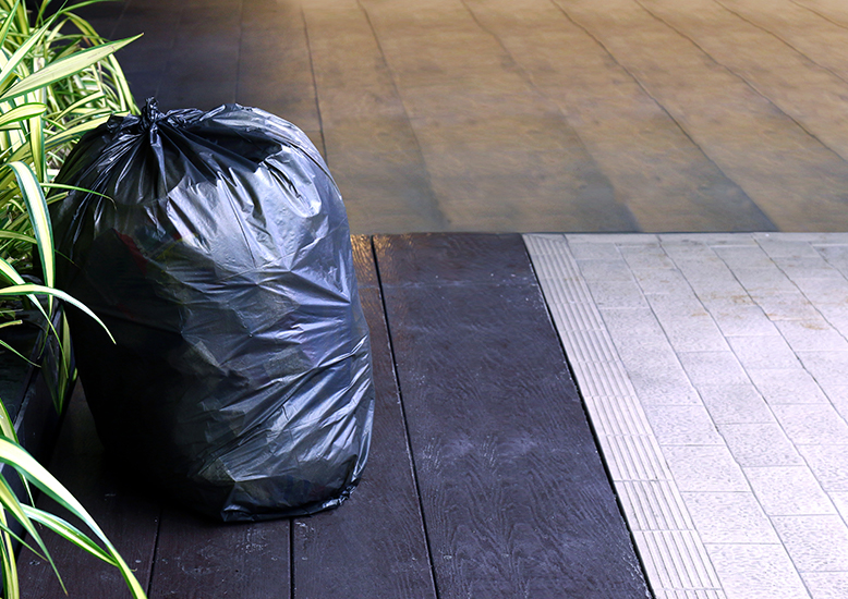 A Garbage bag tied up next to a plant on a wooden floor